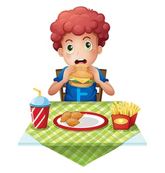 a curly-haired boy eating at a fastfood restaurant vector image