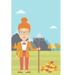 Woman with rake standing near heap of autumn vector