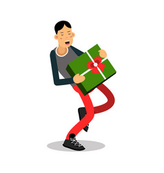 Young smiling man carrying a heavy green gift box vector
