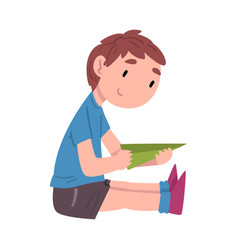 boy sitting on floor and playing with paper vector image