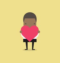 African businessman holding heart shape vector