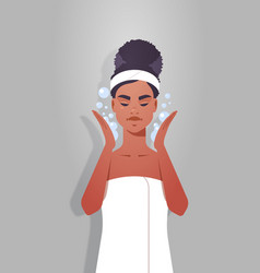 Young woman washing face african american girl vector