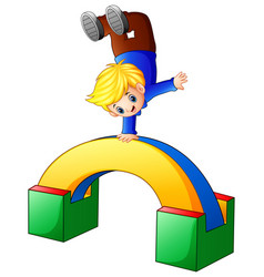 Happy boy upside down on colored wooden toys vector