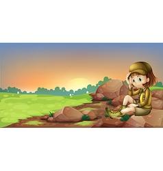A female explorer relaxing above a rock vector