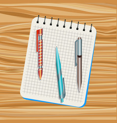 Notebook orange pen blue pen vector