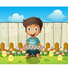 A boy with an empty egg tray and the little chicks vector