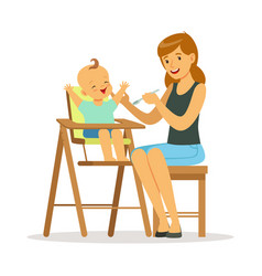 Happy young mother feeding her baby in highchair vector