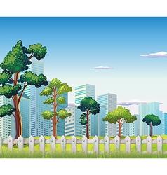 Trees inside fence near tall buildings vector