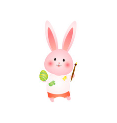 cute rosy easter bunny paints egg with brush vector image