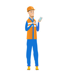 Young caucasian builder holding a mobile phone vector