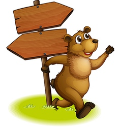 A bear running with a wooden arrow board at the vector image vector image