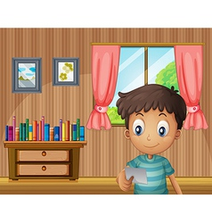 A boy reading a small paper inside the house vector