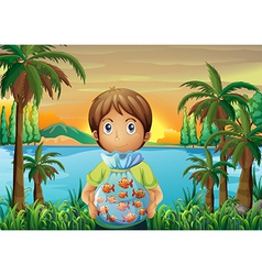 A boy standing near the riverbank while holding vector