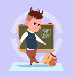 small bad school boy standing over class board vector image vector image