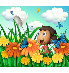 A boy catching butterflies at the flower garden vector image vector image