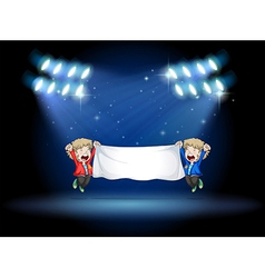 Two boys holding a banner under the spotlights vector image vector image