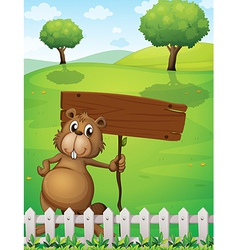 A beaver holding an empty signboard standing near vector image vector image