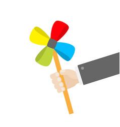 Businessman hand holding paper windmill pinwheel vector