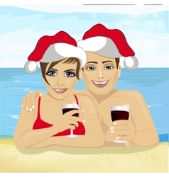 young couple wearing Santa hat lying on beach vector image
