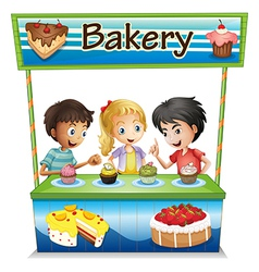 Three kids in a bakery stand with cupcakes vector image