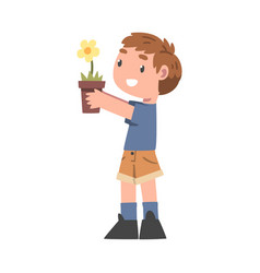 Curious boy holding pot with blooming flower vector