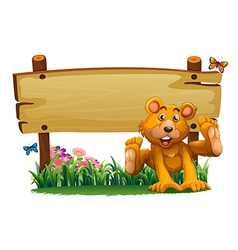 A playful bear near the empty wooden signboard vector image vector image