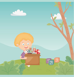 Boy with box full toys in grass park vector