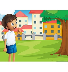 A boy standing near the tree vector