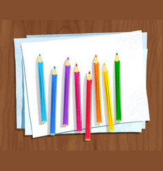 Color pencils lying on paper on brown wooden desk vector