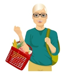 Young man holding a full shopping basket vector