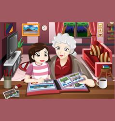 Grandma and granddaughter looking at picture album vector