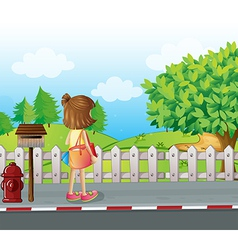 A girl standing near the mailbox at the roadside vector image