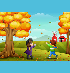 Cute two kids playing with autumn leaves vector