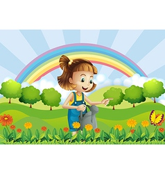 A young girl holding a sprinkler in the garden vector
