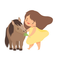 Cute little girl feeding pony with grass adorable vector