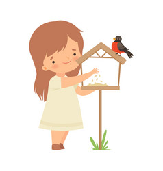 Cute little girl feeding bullfinch with corn vector
