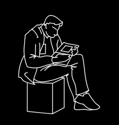 An adult man is reading a book sitting on a cube vector