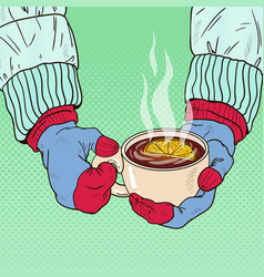 hands in mittens holding mug with hot tea vector image