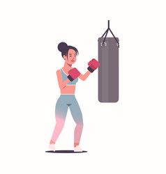Woman boxer doing exercises with punching bag vector