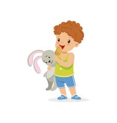 adorable preschool boy holding bunny toy and vector image vector image