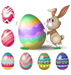 A bunny pushing a big Easter egg vector image vector image
