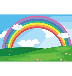 A green landscape with a rainbow in the sky vector