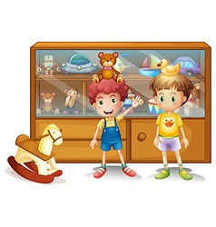 Two young boys in front of a cabinet with toys vector image