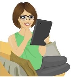 Young woman reading e-book on the sofa vector