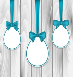 Easter paper eggs wrapping blue bows on wooden vector