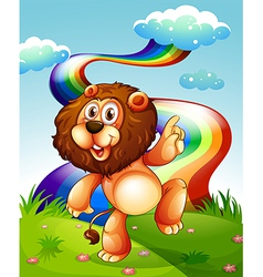 A playful lion at the hilltop and the rainbow in vector image