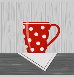 red polka dot cup standing on table with napkin vector image