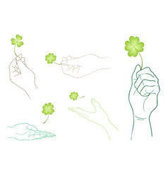 Hand holding four leaf clovers on white background vector