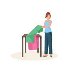 Female seamstress standing near table and folding vector