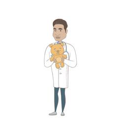 young hispanic pediatrician holding teddy bear vector image